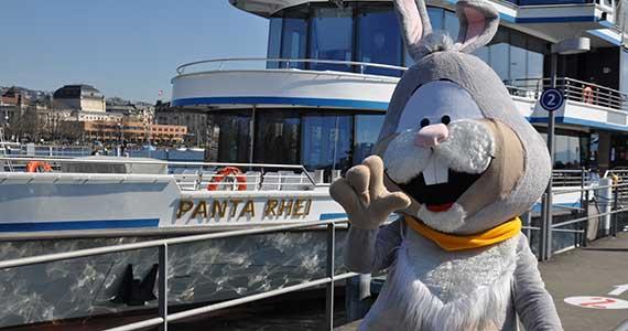 Der Osterhase steht vor dem Schiff Panda Rhein der Zürichsee Schifffahrtsgesellschaft und winkt in die Kamera.
